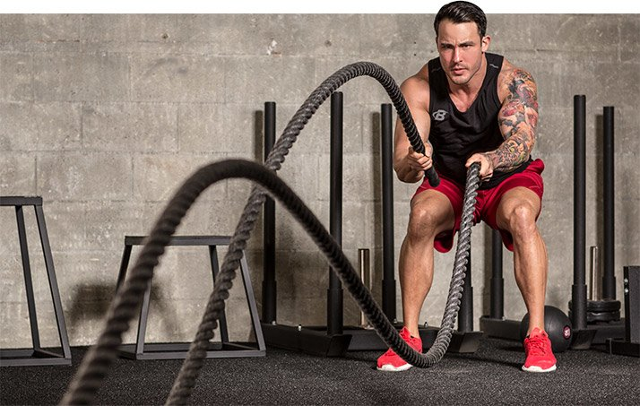 Man working out with battle ropes how to increase your metabolism