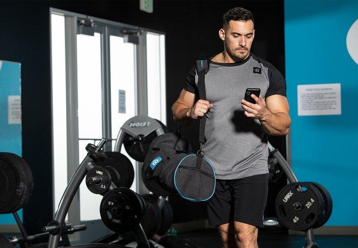 Brian DeCosta walks into the Bodybuilding.com Gym as he checks his phone.