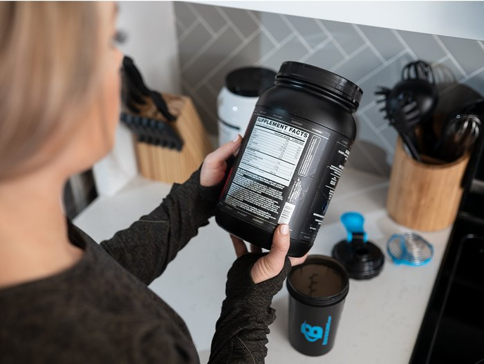Female athlete reading a label on a supplement bottle.