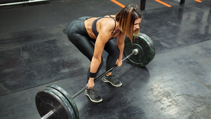 Female athlete preparing to lift a barbell.