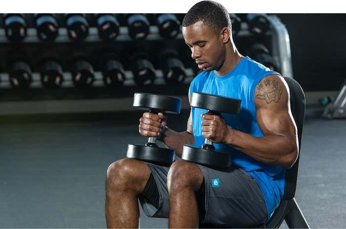 Taking a rest with dumbbells in the gym.