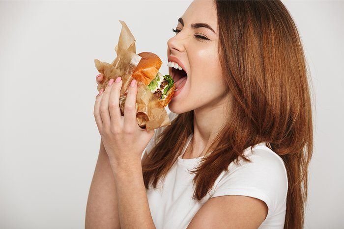 A woman eating a giant hamburger.