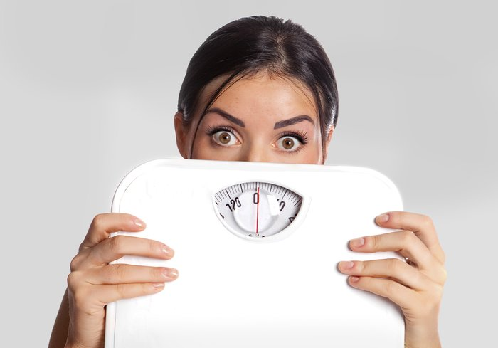 A woman holding a scale.