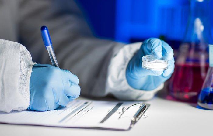 Writing on a notepad while examining a petri dish.
