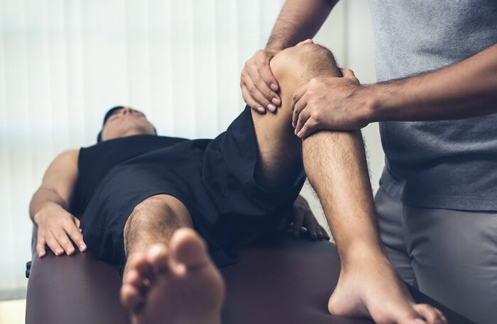 A knee injury being examined by a physical therapist.