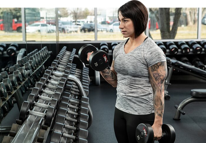 Female athlete performing a heavy dumbbell curl.