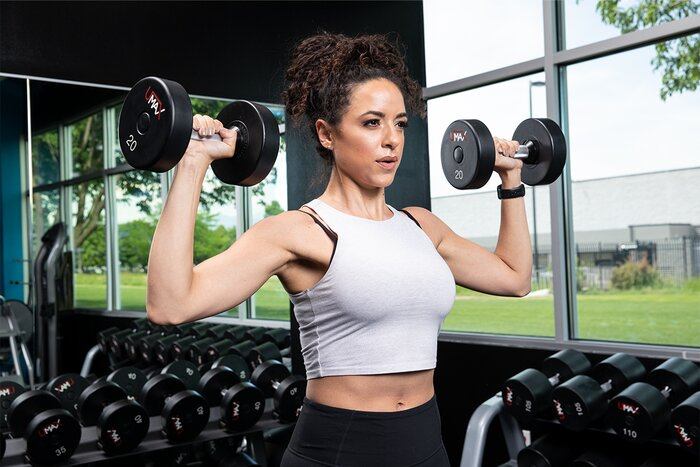 A female athlete performing a standing dumbbell shoulder press.