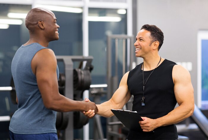 Personal trainer shaking hands with a client