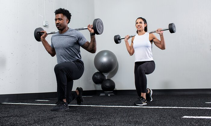 Male and female athletes performing barbell lunges