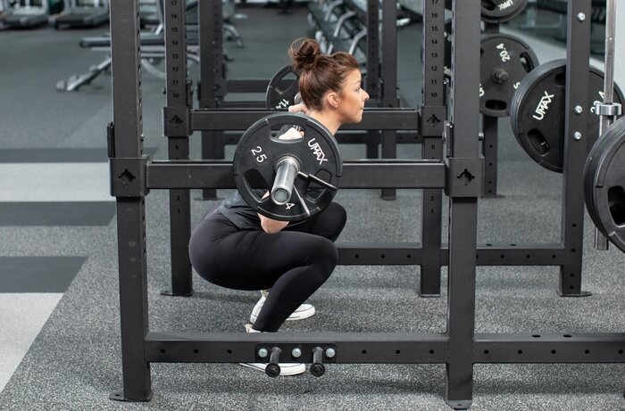 Female athlete performing a barbell squat in the rack.